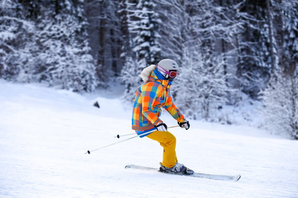 Young female ski rider in motion in winter mountains at ski resort. Man skier in a bright orange suit equipping and mask.