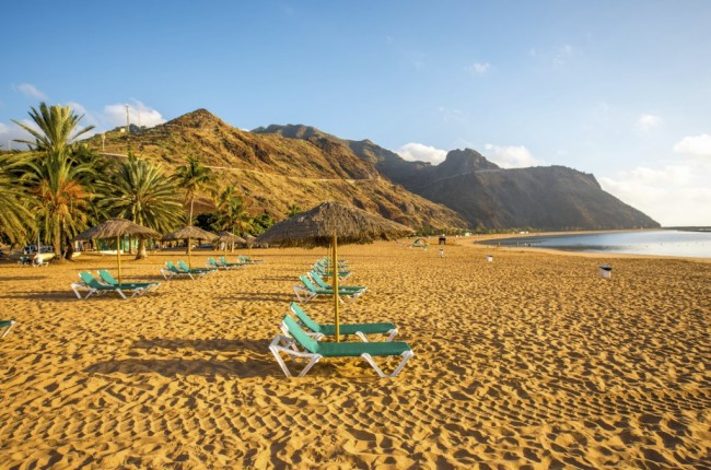 Teresitas beach with sunbeds and mountains on the background on the sunset on Tenerife island, Spain