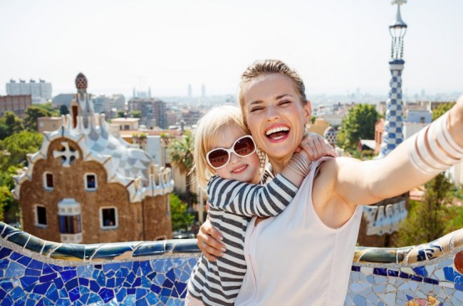 Barcelona will show you how to remarkably spend holiday. Smiling mother and baby taking selfie at Park Guell